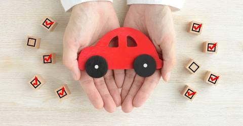 Houten speelgoed auto in handen van een mens en omringd met blokjes waarop wel en geen vinkjes staan